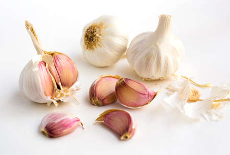 fragrant garlic heads and cloves on white background
