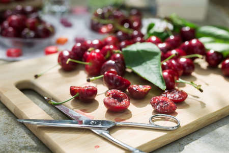 still life of cherries with scissors on a table in the yard
