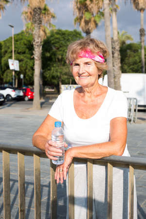 Mature sportswoman leaning her elbow on fence and holding bottle of water in hand.