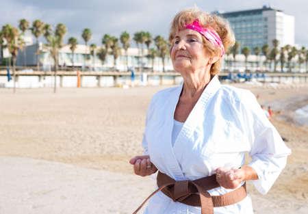 Old woman in kimono exercising karate moves on beach.