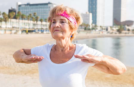 Mature European woman doing fitness exercises on beach.