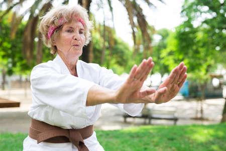 Old lady in kimono performing karate moves in urban park. Stock fotó