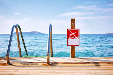 Red no diving sign with copy space on a wooden pier next to a sea ladder in front of a wavy sea and sky background