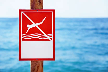Closeup red no diving sign with copy space nailed to a  a wooden plank in front of a blurry wavy blue sea background Stock fotó