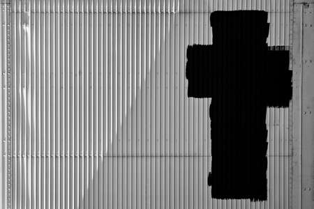 A black cross symbol painted on a textured white metal barrier door