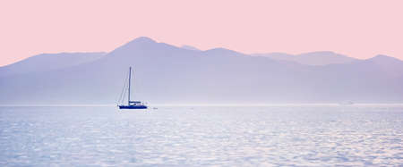 Yatcht sailing over the calm sea and the pastel colors of sunset