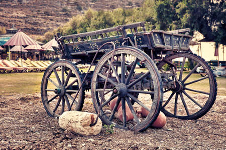 Decorative vintage wooden cart waggon and a stone roller in a holiday place Imagens
