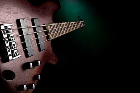 studio shot of a maroon bass guitar on green and black background Standard-Bild