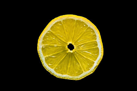close-up shot of a textured lemon slice on isolated black background 免版税图像