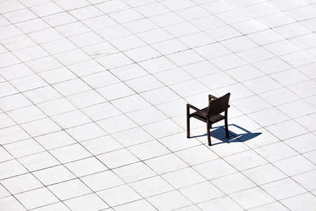 A minimalist view of a single chair and its shadow under the harsh sun on patterned white tile floors