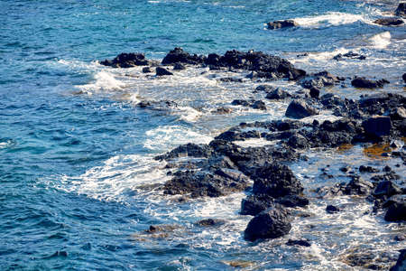 a seashore view with waves hitting the rocks Imagens
