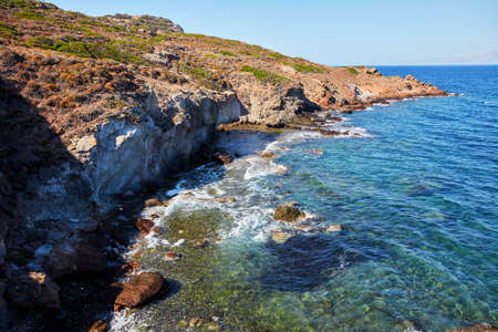 A colorful landscape view of sea, rocks and cliff covered with plants and thorn bushes