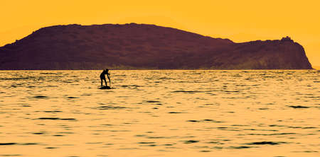 Silhouette of a man paddling on a surfboard in the open sea. He is struggling in front of an island at sunset with beautiful vibrant and pastel colors