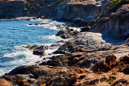 A view of a seashore with rocks, cliff and a turquoise sea in the morning sun Imagens
