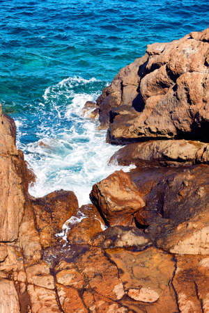 Top down view of cliffs, rocks and a turquoise sea