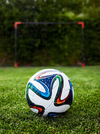 soccer ball on the grass field in front of a goal post 스톡 콘텐츠