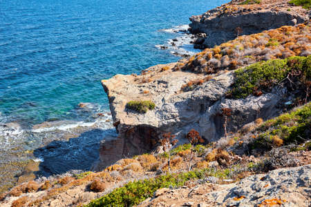 An up high view of sea and cliff covered with plants and bushes in Gumusluk, Myndos, Turkey Imagens