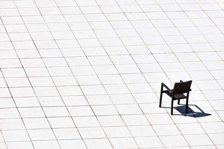 A minimalistic view of a single chair and its shadow on a wide space covered with white tile floors 免版税图像