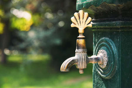 closeup public drinking faucet with an old antique tap in a park 免版税图像