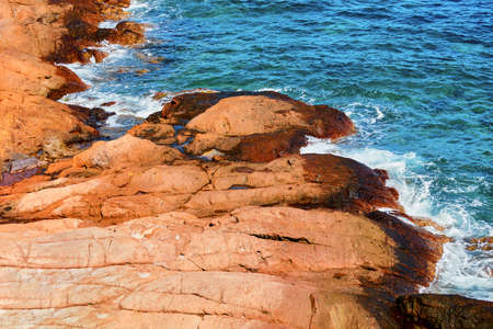 horizontally aligned textured red cliffs and turquoise sea