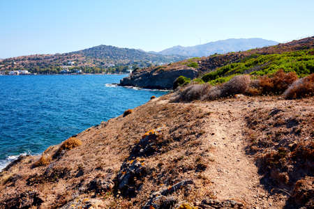 a pathway on a hill near the sea and in the wilderness leading towards Gumusluk Bay, Turkey