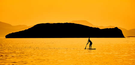 Silhouette of a man paddling on a surfboard in the open sea. He is rowing in front of an island at sundown with beautiful vibrant and pastel colors