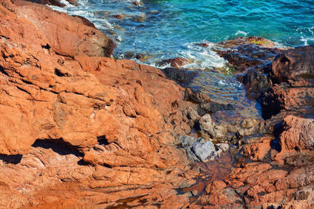 Top down view of red cliffs and rocks. A gap with sea at the bottom. 免版税图像