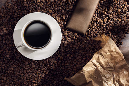 Top classy view of black coffee in a white cup and a chocolate bar on roasted coffee beans spilled form a paper bag on a wooden table Banque d'images