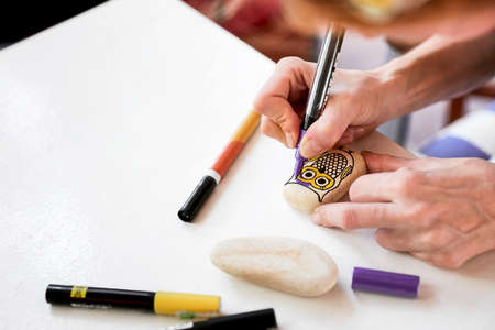 Caucasian woman painting an owl on a stone. Stone paint hobby, arts and crafts.
