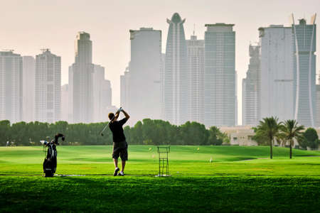 Single man playing golf on the green field facing the skyscrapers