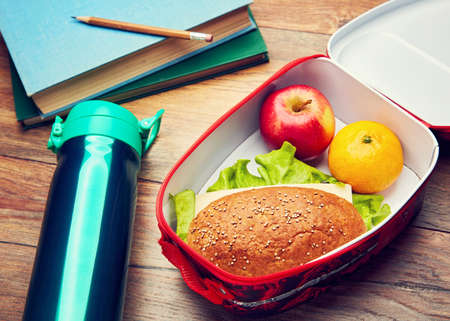 Healthy lunch box with whole wheat bread sandwich, fresh fruits, and water bottle on a wooden desk. Concept of school lunch break. 免版税图像