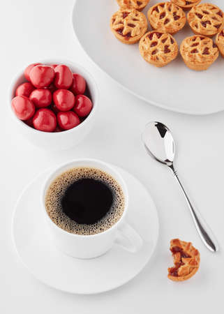 Coffee, white cup, spoon, red sugar coated pills and small apple tarts on a white table. Minimalist concept of coffee time.