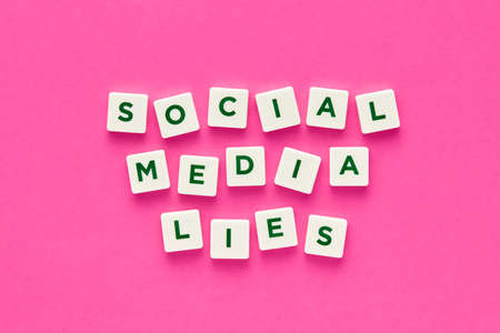 Social media lies words written with green letters on white square buttons on pink background. Concept of social media deception and dishonesty.