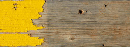 Single old wooden planks with worn yellow paint on it. For backdrop or text placement use.