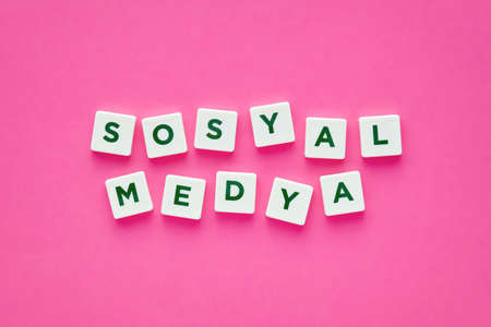 Social media words written in Turkish with green letters on white square buttons on pink background. Concept for online dating. Foto de archivo
