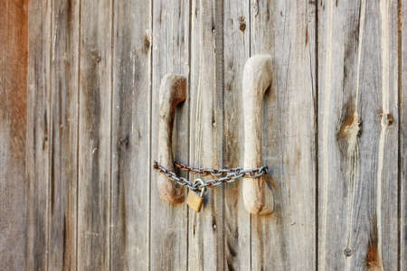 Close up view of an old wooden barn door locked with rusty chain and padlock Stock fotó