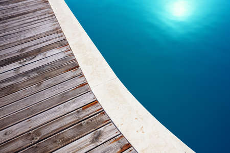 Minimalist close up view of a swimming pool and the composite wooden flooring of its deck. Holiday and relaxation.