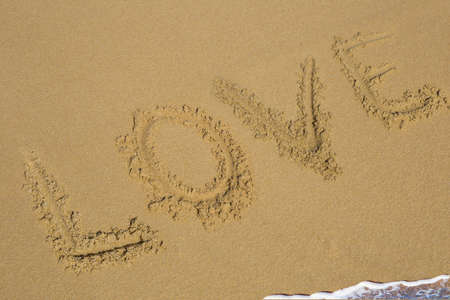 Love and heart symbol handwritten on tropical beach with soft wave on background Stockfoto - 97949352