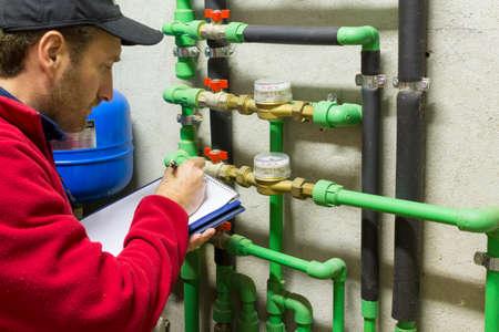 plumber: fontanero en el trabajo haciendo que la medición del consumo Foto de archivo