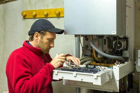 condensing: plumber repairing a condensing boiler Stock Photo