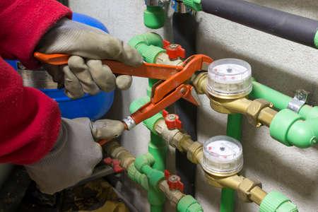 fontanero: Fontanero en el trabajo de instalar un contador de agua