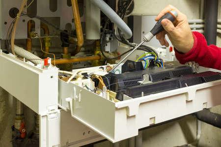 condensing: electrician repairing a condensing boiler