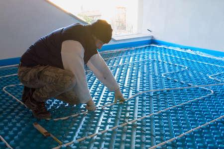 radiant: Plumber working system installed radiant floor