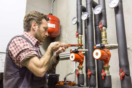 condensing: plumber at work installing a circulation pump