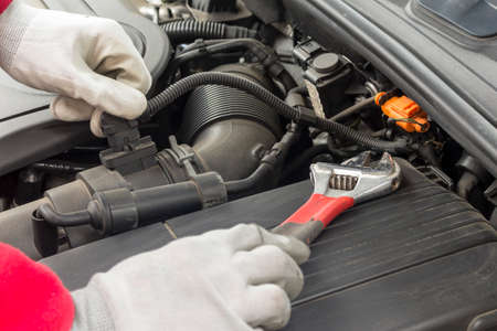 mechanician: Mechanician performing maintenance on a car engine Stock Photo