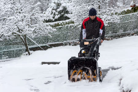 blower: man removing snow with a snow blower