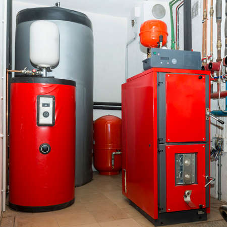 Firewood boiler and puffer thank in the boiler room Standard-Bild