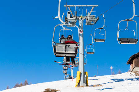 skiers: skiers on chairlift with snowy mountains in the background