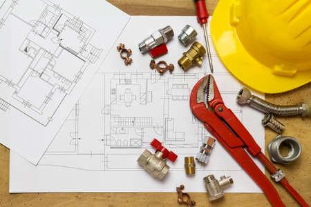 Bureau met hydraulische hulpstukken, helm en projectontwerp Stockfoto