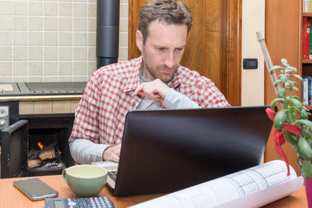 warm shirt: Young man works remotely through internet connection